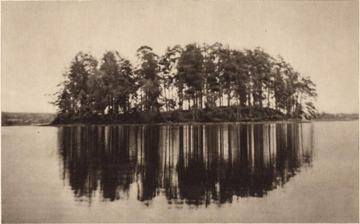 <bHusholmen vid Lidboholm (Ön) i sjön Örken sedd från öster. Pålverket till den långa bron går (under vattnet) till vänster. <bTill höger ligger den lilla Galgholmen, ej synlig å bilden. — Foto: Nils Olsson 1938.