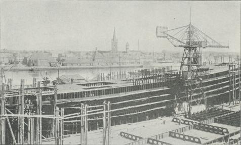 Fig. 12. Skibsværft med 2 Nybygninger, hvoraf den ene er spanterejst og Klædning og Dæk delvis anbragt,<bmedens den anden lige er paabegyndt og kun Bundstokke delvis paa Plads.